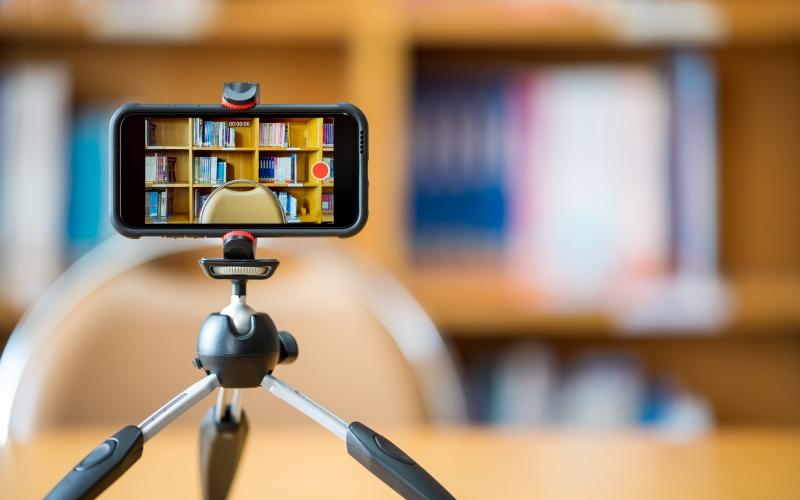 un smartphone sur un trépied devant une bibliothèque