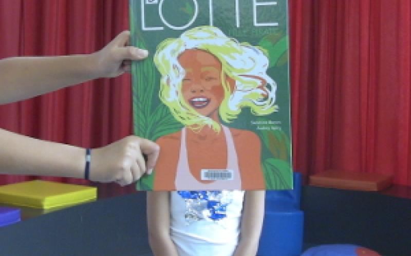 Une jeune fille par un trucage photographique  a pour visage la couverture d'un album qui représente une jeune fille . C'est un book face