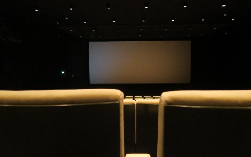 Une salle de cinéma avec une lumière tamisé équipée de fauteuil jaune à l'apparence très confortable
