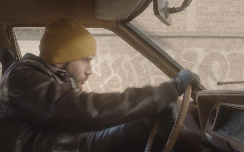 un jeune homme barbu , avec un bonnet jaune et un blouson en cuir est a l'arrêt au volant d'une vielle voiture.