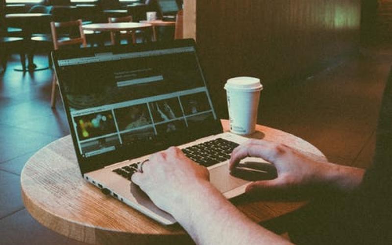 Un jeune homme tape sur son ordinateur dans un café
