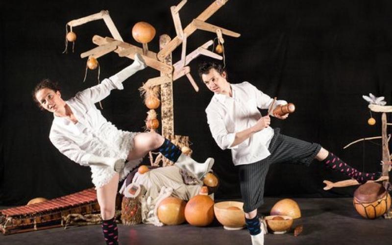 Deux danseurs se trouvant devant un arbre et des calebasses